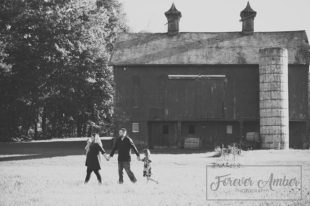 black and white with barn and family walking by