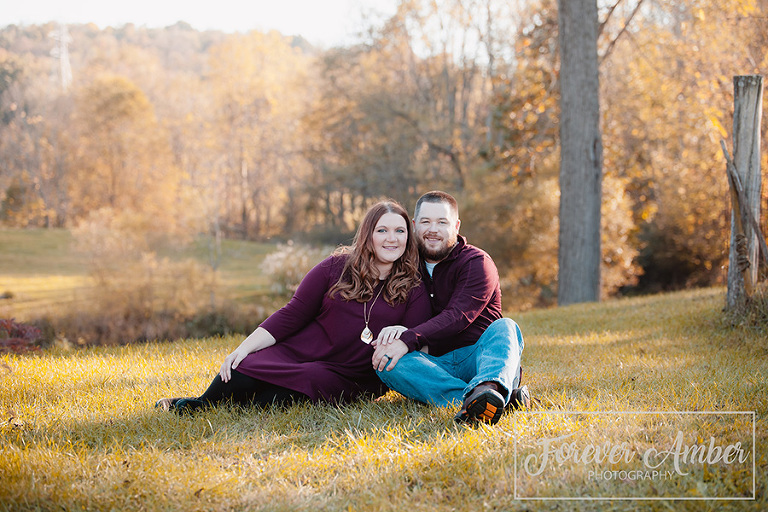 Couple sitting in grass with glowing fall colors