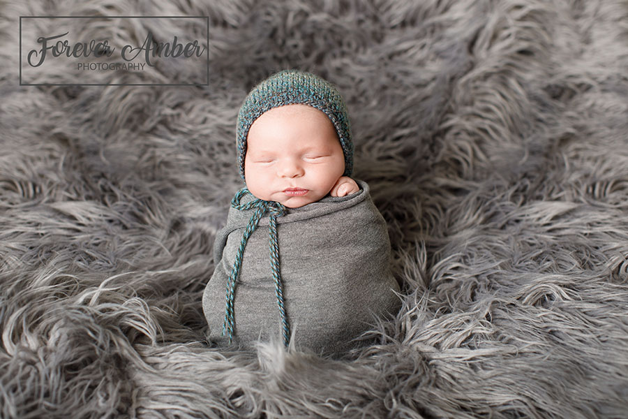 Potato Sack Pose on gray fur in a gray wrap with knit teal bonnet