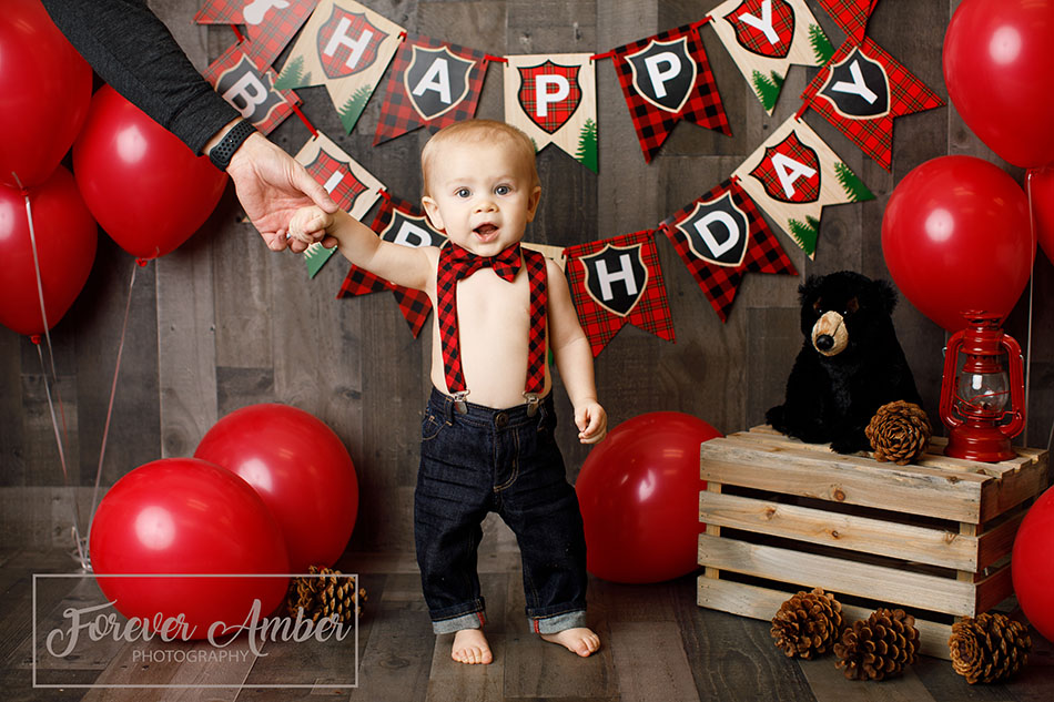 boy standing with fathers hand wearing suspenders in buffalo plaid