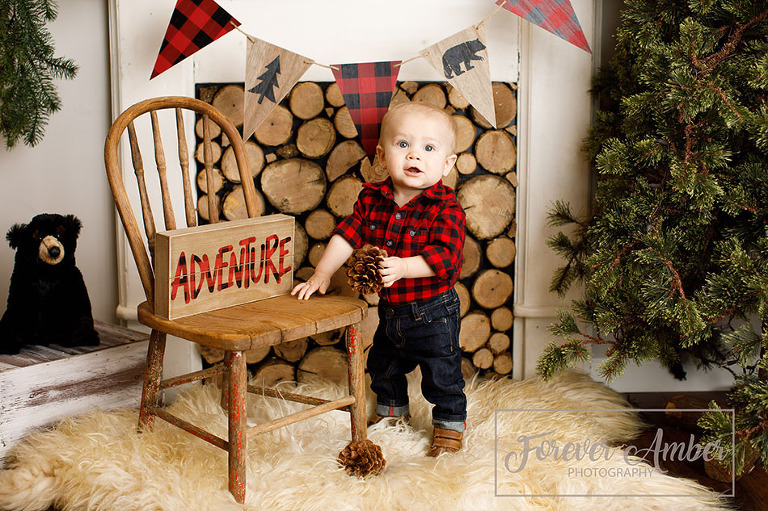 Boy in buffalo plaid standing in front of log fireplace