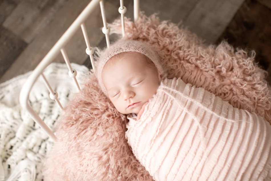newborn baby girl in pink on baby bed