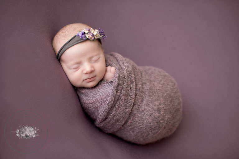 Newborn swaddled in purple on purple backdrop