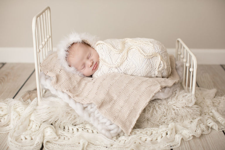 Winter swaddled baby in fur bonnet on baby bed with neutral layers