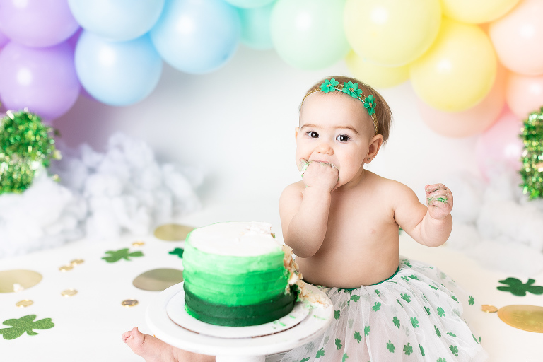 st. patricks day first birthday set with baby eating cake